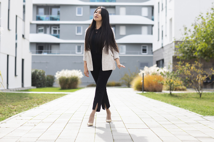 Woman with high heels  outside in front of new buildings