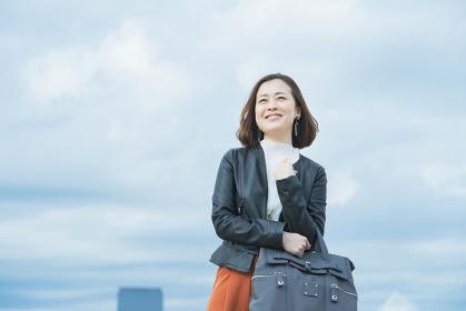 笑顔で通勤するカジュアルな服装のビジネスウーマン