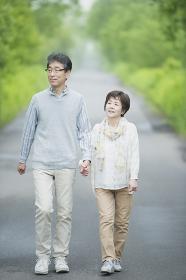 一本道を歩くシニア夫婦