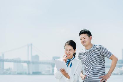 タブレットPCを使うカップル(30代・デート・外出)