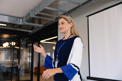 Front view of a Caucasian woman with long blond hair, wearing smart clothes, standing in an empty modern meeting room, training her speech for conference.