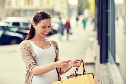 happy pregnant woman with shopping bags at city