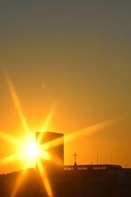 夕陽とビルと教会の十字架