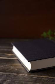 木のテーブルの上に置かれたハードカバーの本
