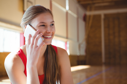 Close up of smiling female basketball player talking on phone
