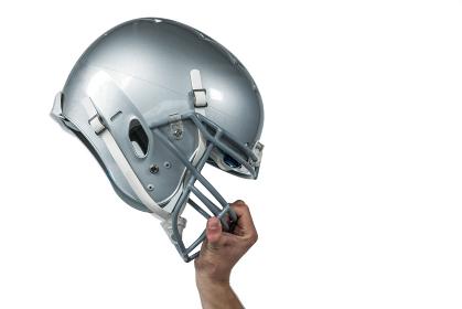 American football player handing his sliver helmet