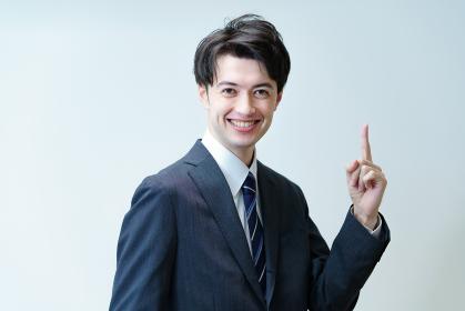 人差し指を立てるポーズをするビジネスマン