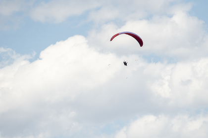 Paragliders soar high in the sky on a sunny day in the Coast Mountains of BC.
