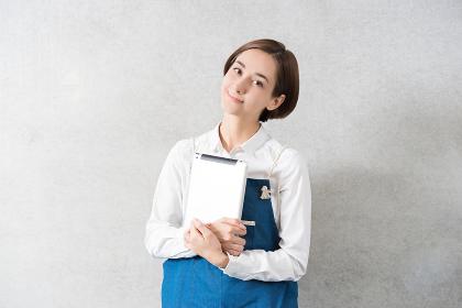エプロン姿でタブレットPCを持つ女性