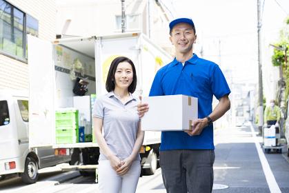 荷物を手渡す男性スタッフと、受け取る女性