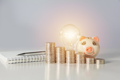 Energy saving light bulb with piggy bank and stacks of coins on table. Financial and saving concept.