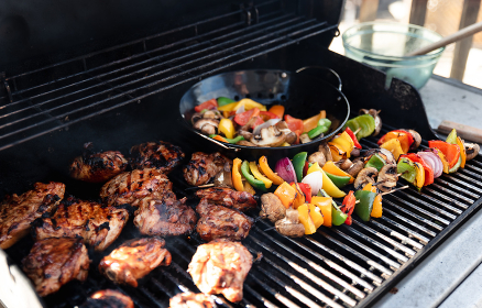Vegetable skewers and chicken on the grill of a gas bbq.