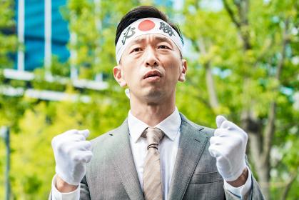 「必勝」の鉢巻を巻いてガッツポーズする男性