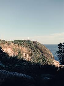 崖の上から見える海と灯台(日本・高知県・足摺岬)