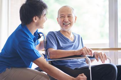 車椅子に乗る高齢者と介護士