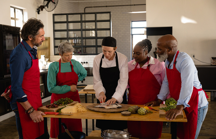 Side view of a multi-ethnic Senior group of adults at a cookery class, the diverse adult students listening to instructions from a Caucasian female chef wearing chefs whites and a black hat and apron, standing around a wooden table of ingredients