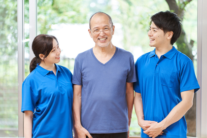 笑顔で立つ介護士と高齢者