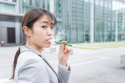 電子タバコを吸う若いビジネスウーマン