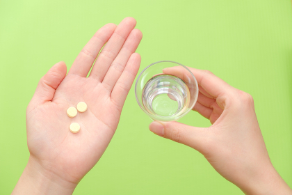 錠剤を持つ手 水 コップ 医薬品