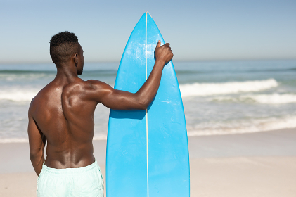 A rear view of an attractive African American man enjoying free time on beach on a sunny day, smiling, having fun, standing with his surfboard, sun shining on him.