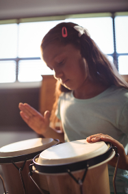 Girl practicing bongo drums in classroom