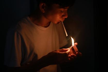 マッチでタバコに火をつける男性