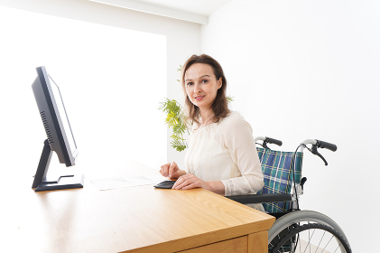 車椅子でデスクワークをする外国人の女性