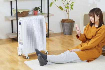 オイルヒーターで体を温める日本人女性
