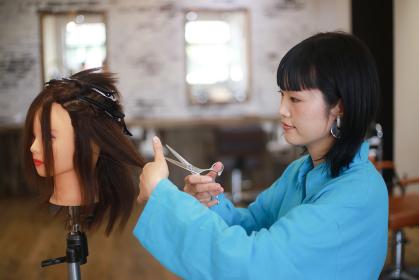 髪を切る練習する美容師 イメージ