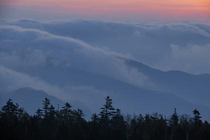 夜明けが迫る山々に朝の雲がまとわりつく