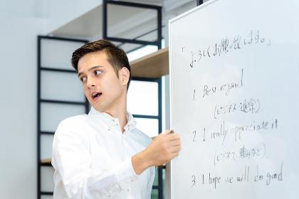 ホワイトボードで英語を教える外国人男性講師