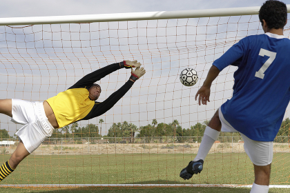 Player Scoring Goal While Goalkeeper Diving To Save It