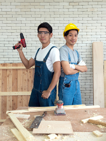 Two Asian carpentry poses confidently before beginning the job