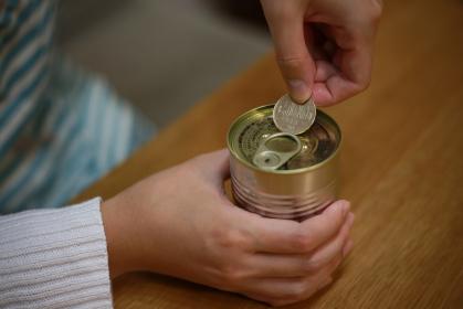500円硬貨で缶詰を開ける女性