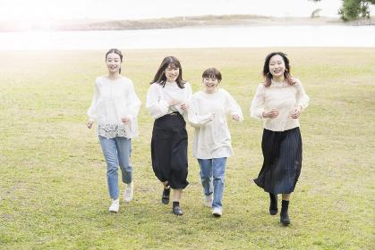 笑顔で話しながらゆっくり走る女性4人