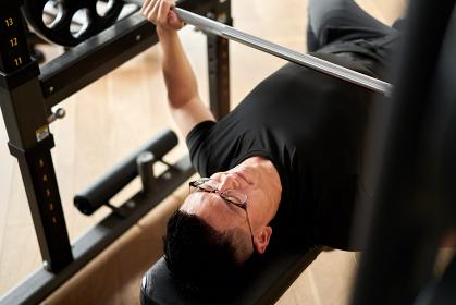 トーレーニングジムでベンチプレスをするアジア人男性