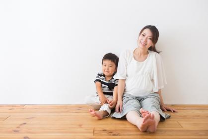 フローリングに座る男の子と妊婦さん