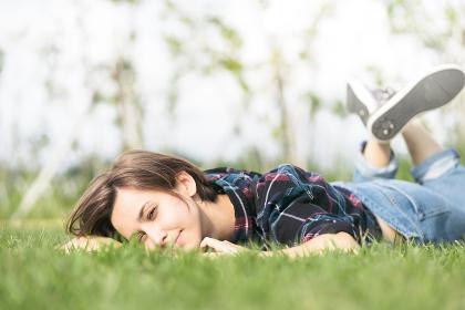 芝生に寝そべる笑顔の女性