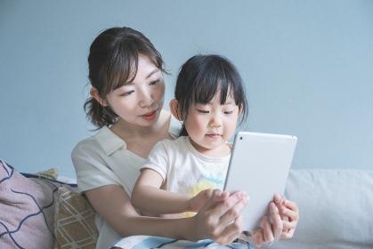 ソファに座ってタブレット端末を操作するお母さんと娘