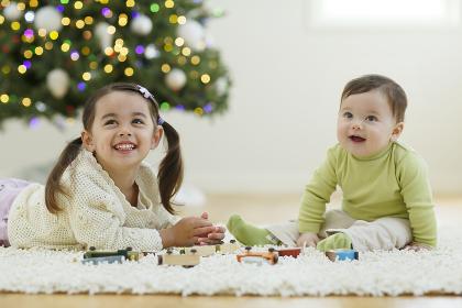 クリスマスツリーのあるリビングで遊ぶきょうだい