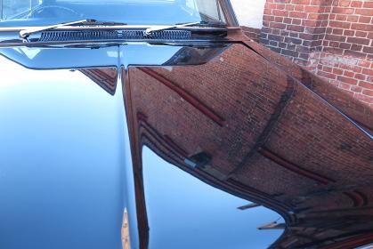 古い車のボンネットに映っている煉瓦塀