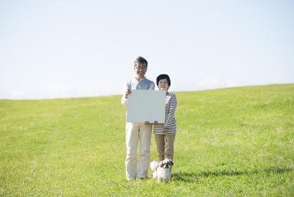 草原でメッセージボードを持つシニア夫婦と犬