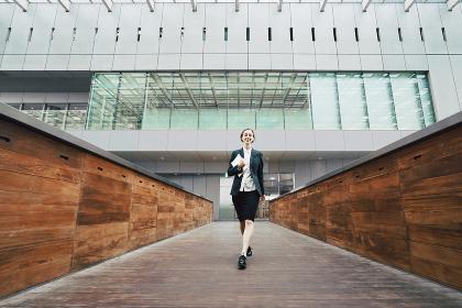 颯爽と歩く女性(ビジネスイメージ・タブレットPC)