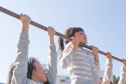 鉄棒をする小学生