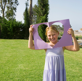 Young girl holding paper heart frame