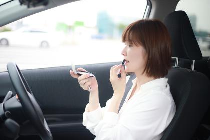 車内で化粧する女性