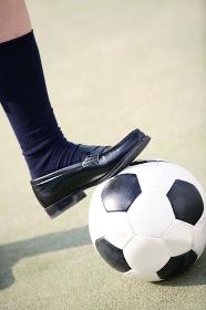 サッカーボールを止める女子高校生の足