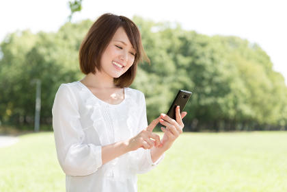 スマートフォンを見る女性 屋外