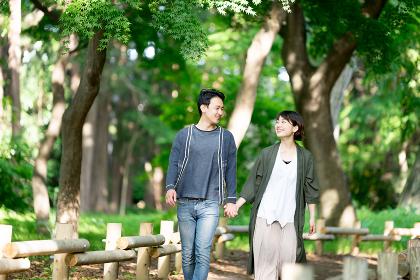 デートで新緑の爽やかな小道を散歩するカップル