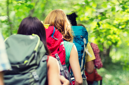 close up of friends with backpacks hiking